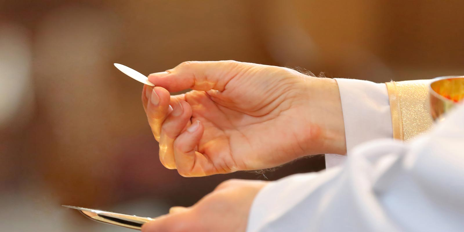A priest hand presenting the Eucharist