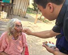 Father Viet Hoang visits a sick woman in Paragraph and provides the Eucharist