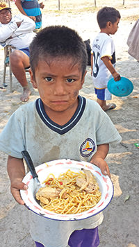 A hungry child in Bahia Negra, Paraguay receives received a donated meal