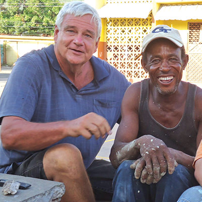 Brother Bernie Spitzley sitting with a local resident in Jamaica