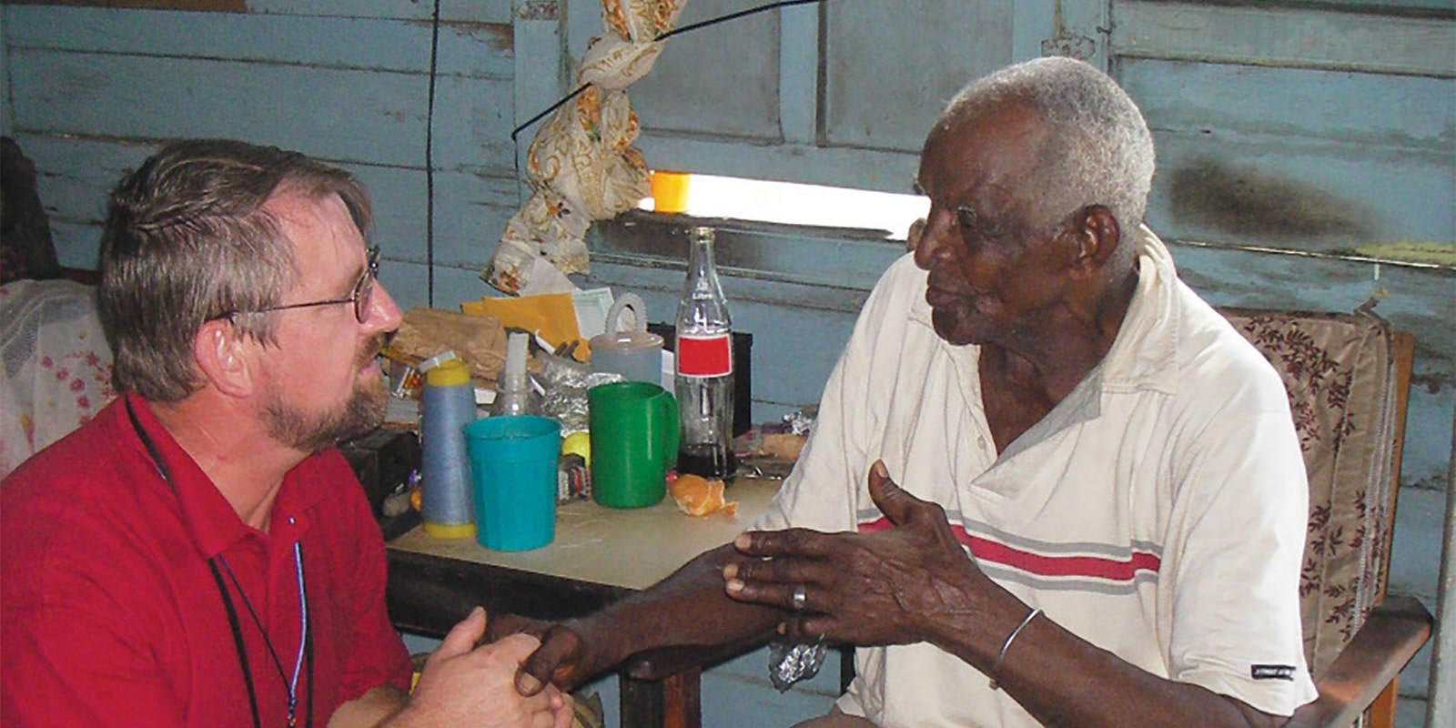 Father Bernard Latus in Jamaica listening to the concerns of a local resident - Society of the Divine Word Chicago Province