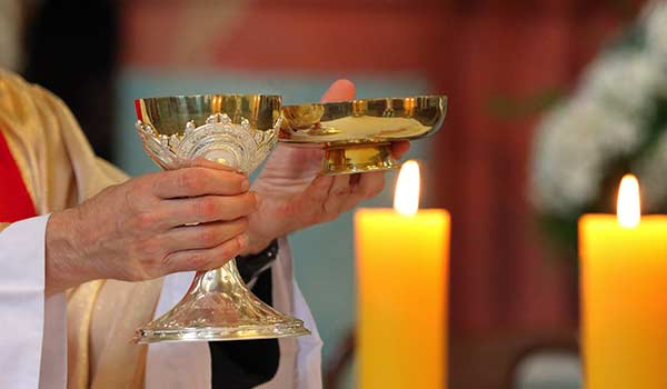 A priest holds a chalice with a candle in the background