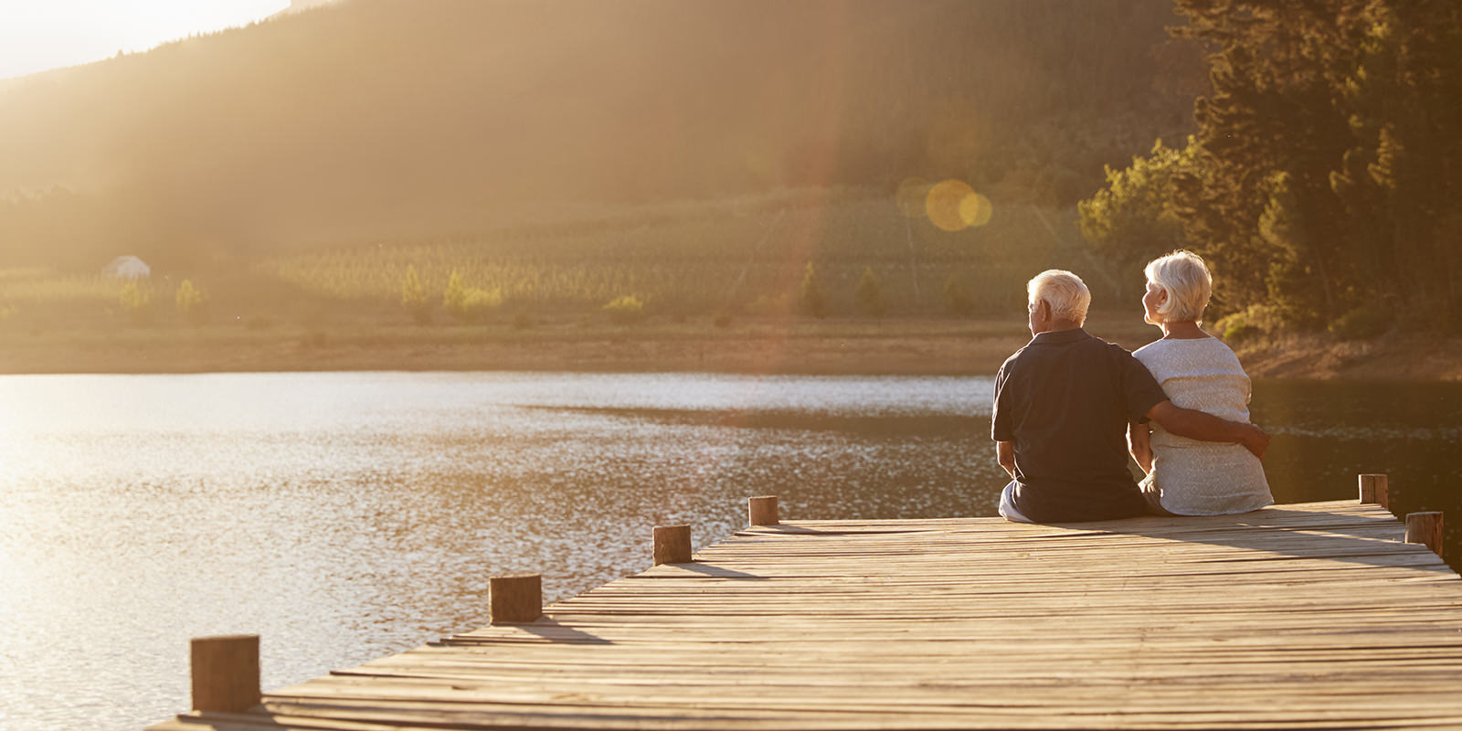 An older retired couple sits at the end of a pier on lake enjoying the scenery
