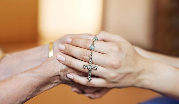 Two people holding hands with rosary - 350x600