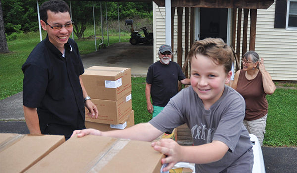 Father Thien Duc Nguyen getting help from a young volunteer for a food pantry in West Virginia - Society of the Divine Word Chicago Province